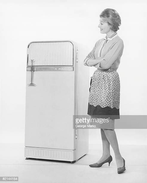 Woman in apron looking at refrigerator, (B&W)