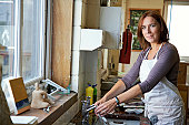 'Woman in art classroom, washing palette at sink, portrait'