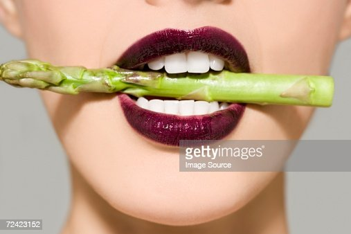 Woman in asparagus in her mouth : Stock Photo