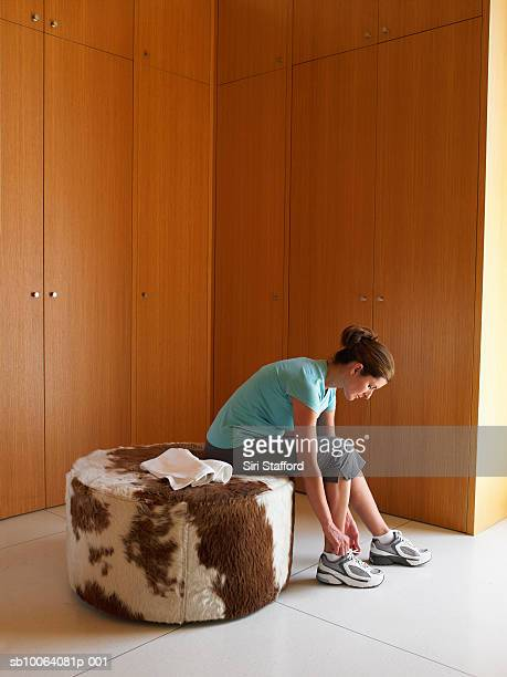 Woman in athletic clothing adjusting shoe