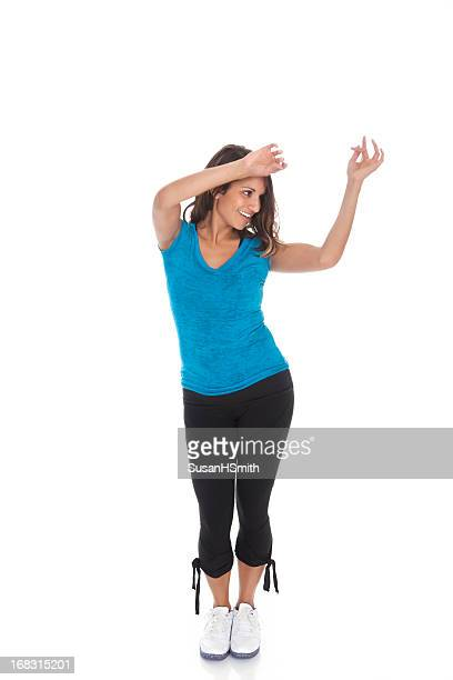 Woman in athletic wear dancing against white background