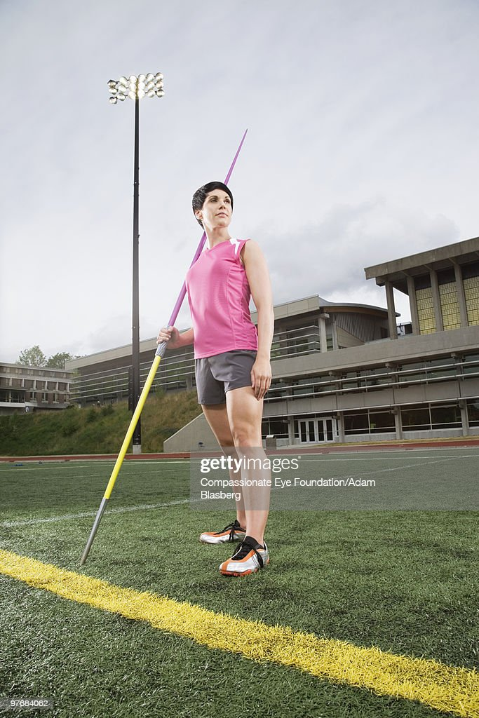 Woman in athletic wear holding a javelin : Stock Photo