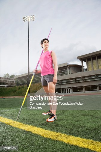 Woman in athletic wear holding a javelin : ストックフォト