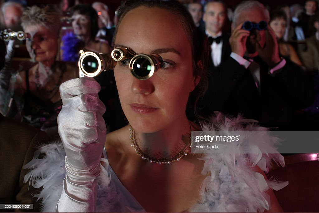 Woman in audience using opera glasses : Stock Photo