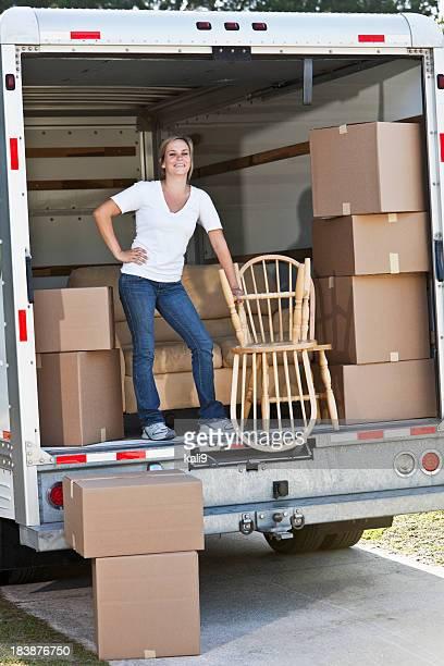 Femme en arrière de Camion de déménagement avec boîtes et un mobilier