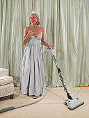 Woman in ball gown pretending to be surprised while vacuuming bedroom rug