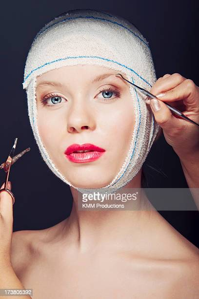 Woman in bandages having makeup applied