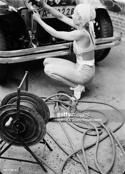 Woman in bathing costume cleans headlights of car Photographed by Zoltan Glass c1930 Photograph taken for advertisement series in the early 1930's by...