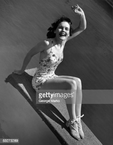 Woman in bathing suit sitting on diving board waving : Stock Photo