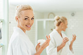 beautiful young woman in bathrobe holding container with face cream and smiling at camera
