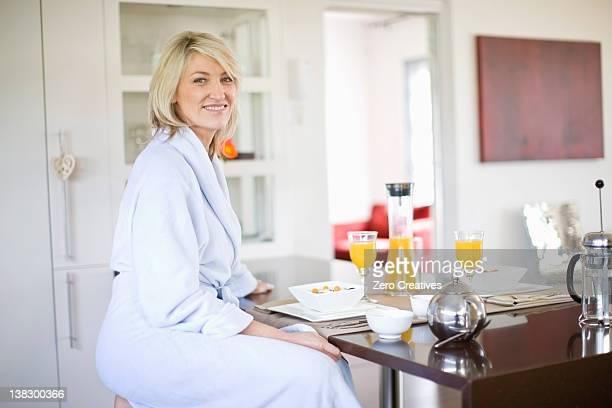 Woman in bathrobe at breakfast table