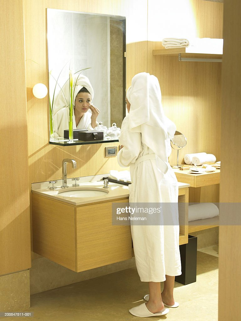Woman in bathrobe cleaning face in mirror in bathroom, rear view : Stock Photo