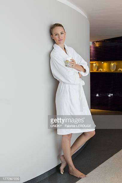 Woman in bathrobe drinking lemonade at spa