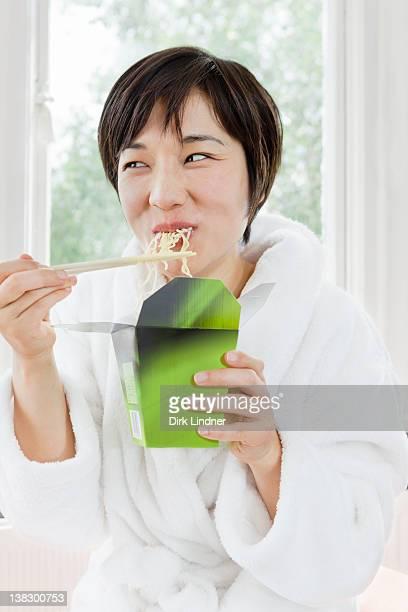 Woman in bathrobe eating Chinese food