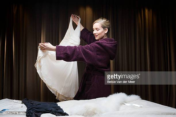 Woman in bathrobe holding up dress