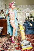 Woman in bathrobe smoking cigarette while cleaning living room with vacuum cleaner