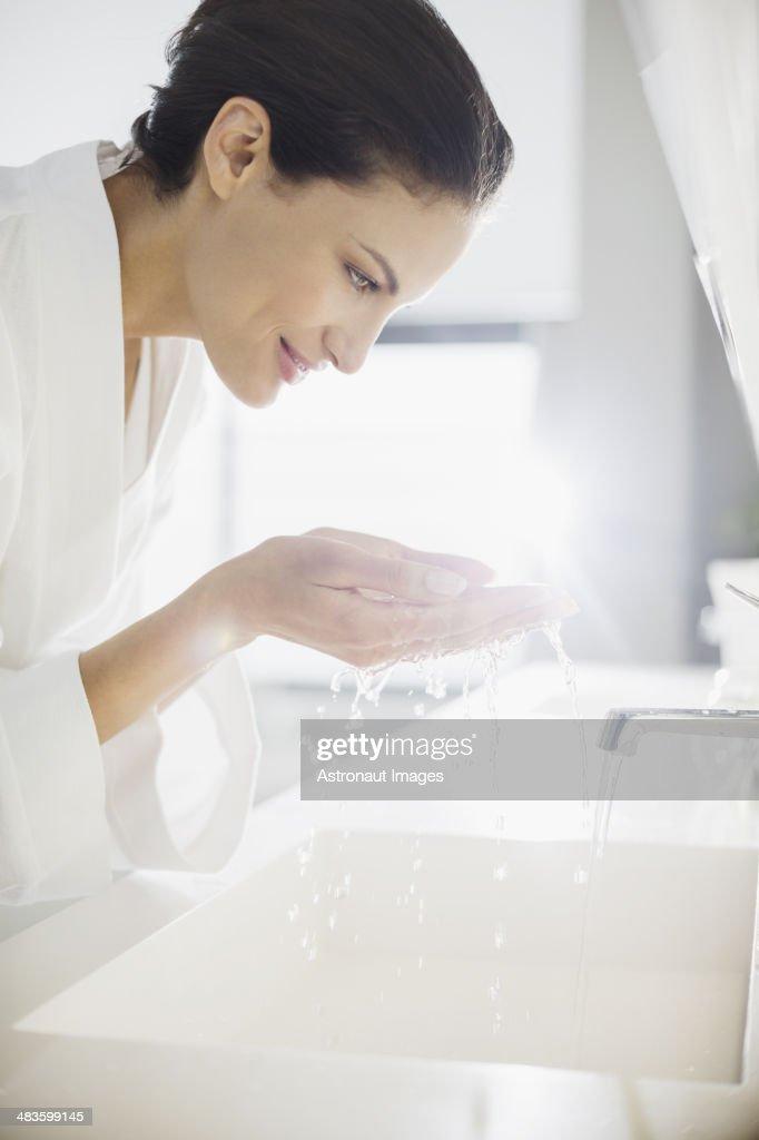 Woman in bathrobe splashing water on face