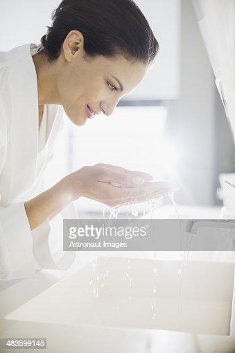Donna in accappatoio spruzzi d'acqua sul viso
