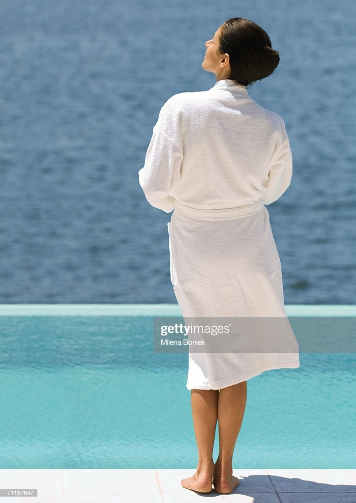 Woman in bathrobe standing near pool overlooking sea, rear view