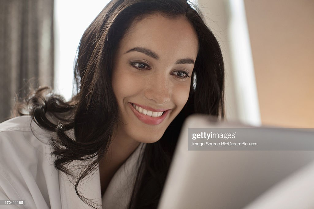 Woman in bathrobe using tablet computer : Stock Photo