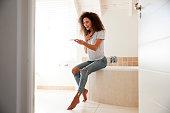 Woman In Bathroom Celebrates Positive Home Pregnancy Test Result