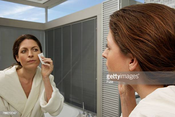 Woman in Bathroom Removing Make-Up