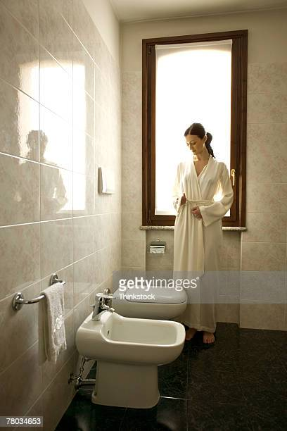 Woman in bathroom with bidet and urinal