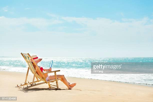 Femme en chaise de plage de lecture sur un e-book tablette vacances à Hawaï