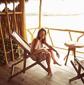 Woman in beach chair, smiling, portrait