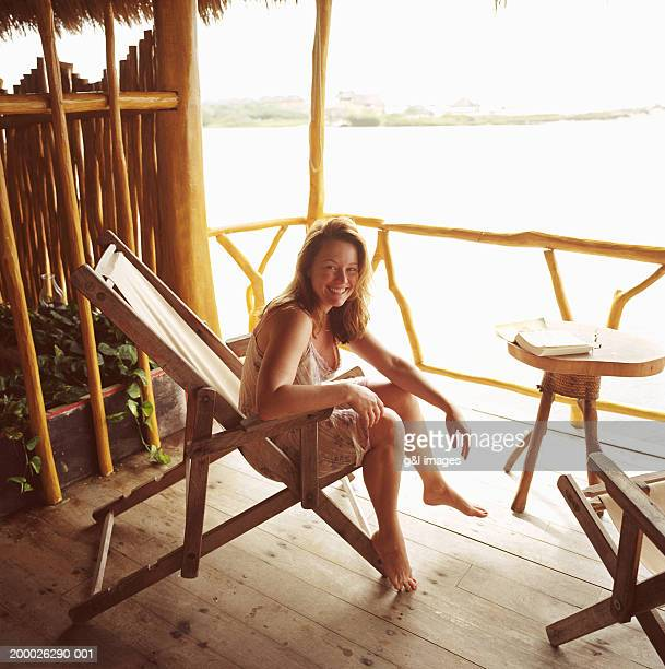 Woman in beach chair, smiling, portrait