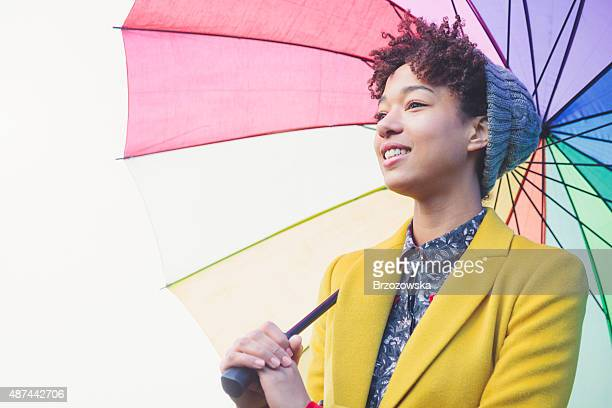 Woman in beanie hat under colorful umbrella (London, UK)