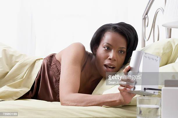 Woman in bed holding alarm radio