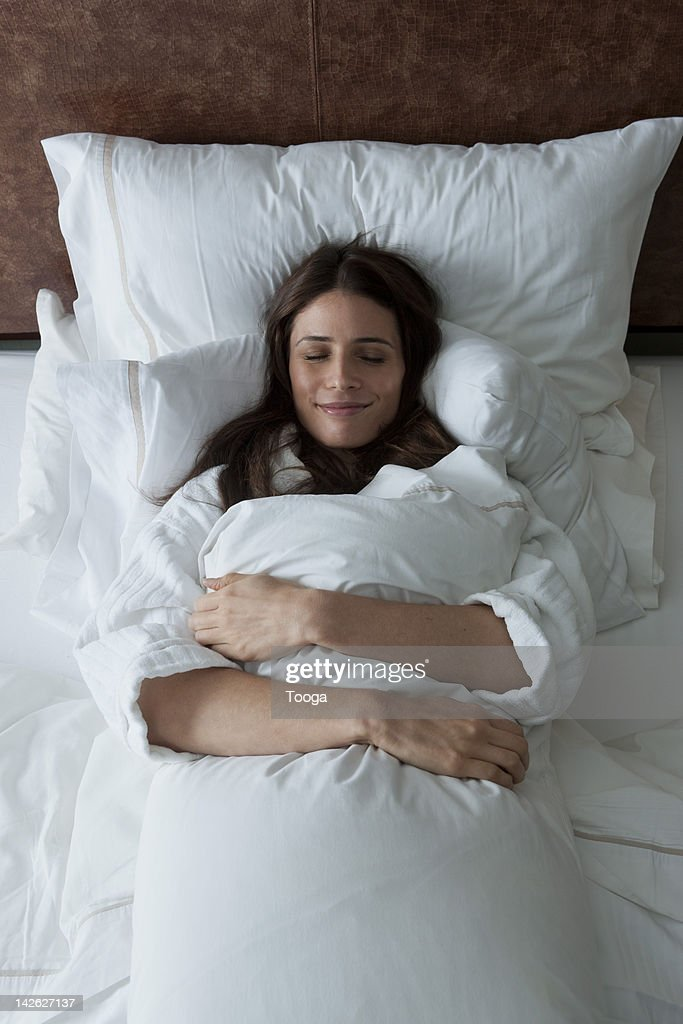 Woman in bed hugging pillow