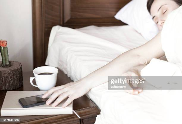 Woman in bed reaching for her mobile phone