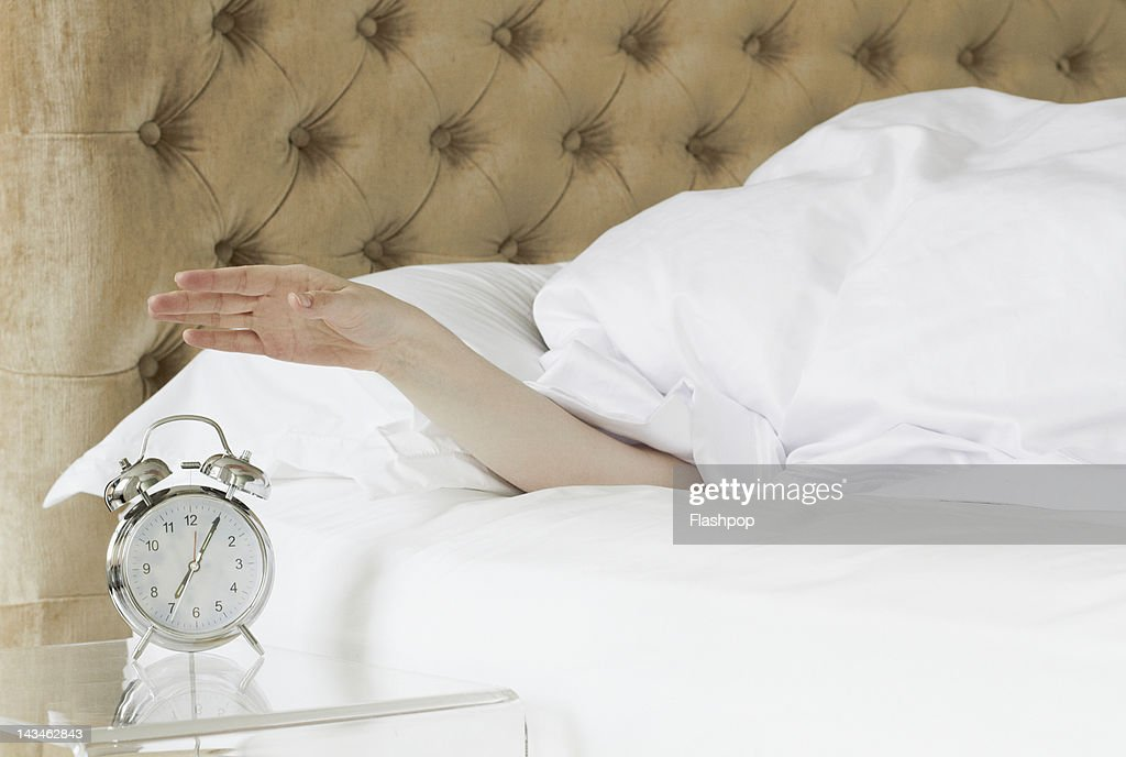 Woman in bed reaching out to alarm clock