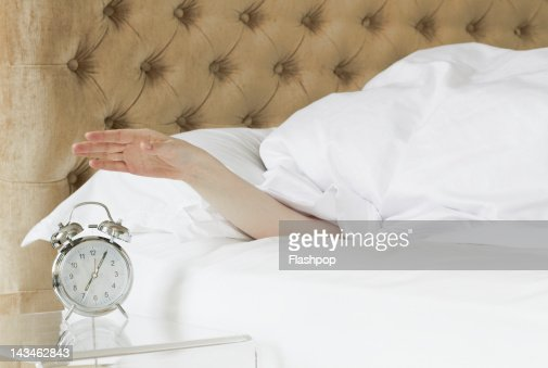 Woman in bed reaching out to alarm clock : Stock Photo