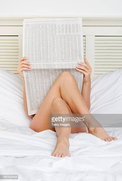 Woman in bed reading business section