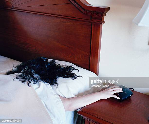 Woman in bed turning off alarm, rear view