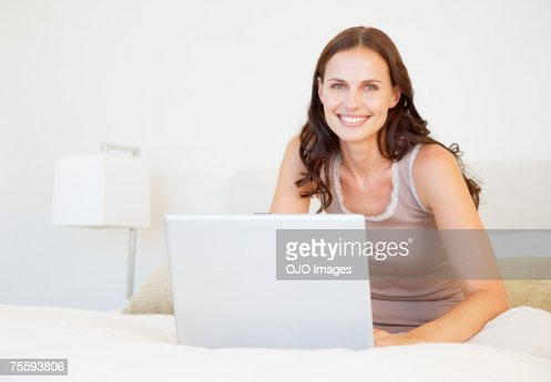 Woman in bed using a laptop : Stock Photo