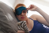 Young woman with sleep mask waking up in bed and snoozing alarm clock on cell phone, mobile telephone. Girl sleeping in bedroom at home and waking up after receiving text message or call on smartphone