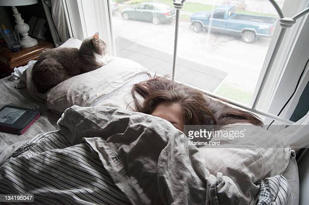 Woman in bed with face covered