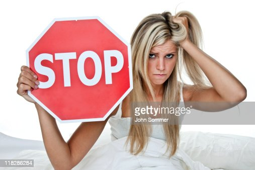 Woman in bed with sign that says STOP
