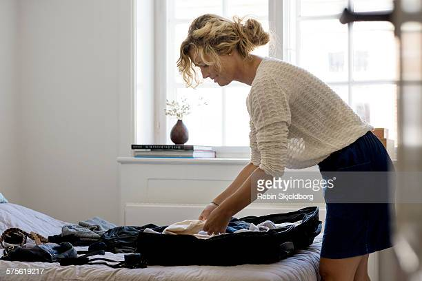 Woman in bedroom packing suitcase