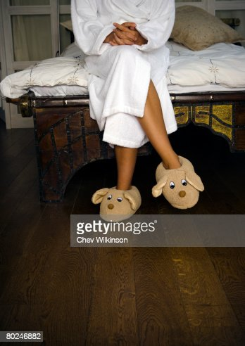 Woman in bedroom with toy slippers.
