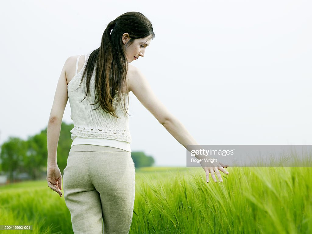 Woman in beetroot field, arm outstretched, rear view