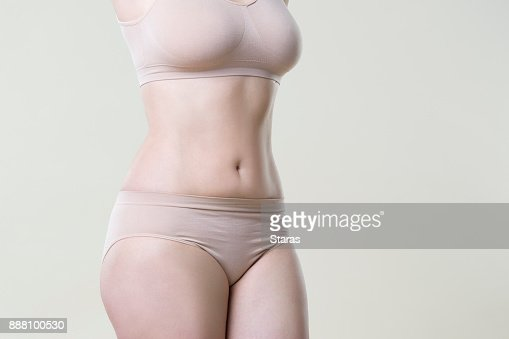 Woman in beige underwear on studio background, perfect female body : Stock Photo