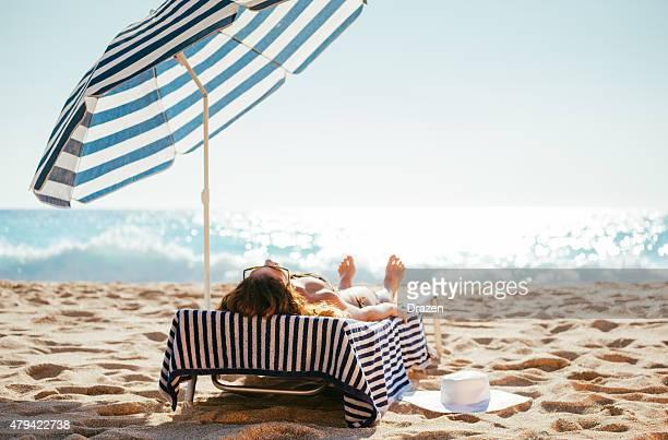 Donna in bikini e sdraiarsi sulla spiaggia in estate suntanning