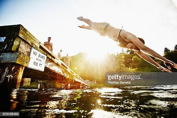 Woman in bikini diving off of dock into lake