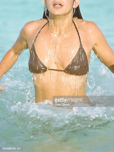 Woman in bikini emerging from water, mid section