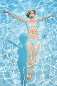 Woman in bikini floating in pool